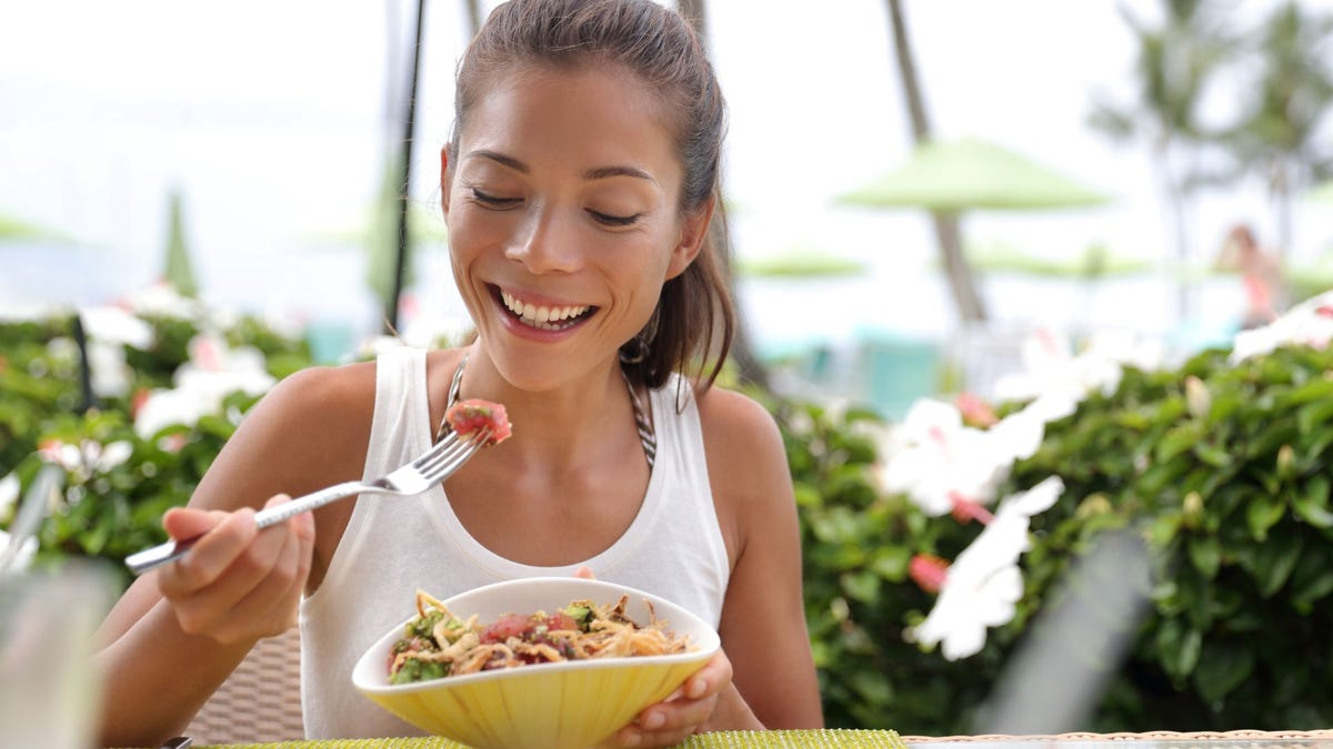 A woman eating salad.