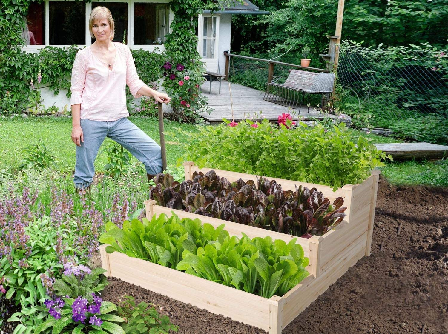 A woman stands next to a three-tiered raised wood garden bed filled with leafy plants