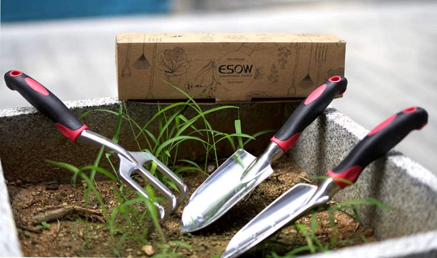 A garden rake, a trowel, and a transplanting shovel sit in a small dirt garden bed