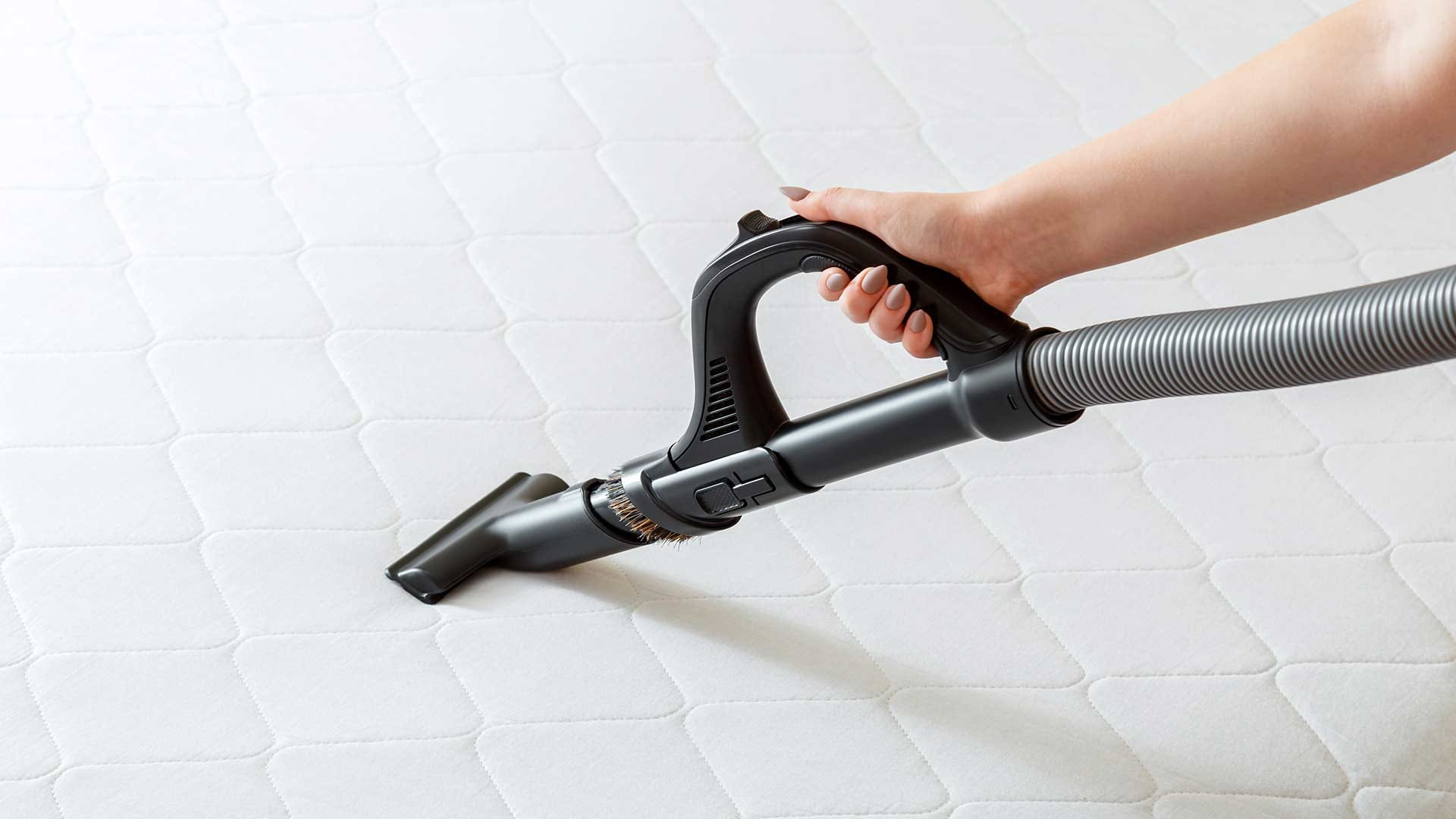 A woman vacuuming a bare mattress with a vacuum hose.