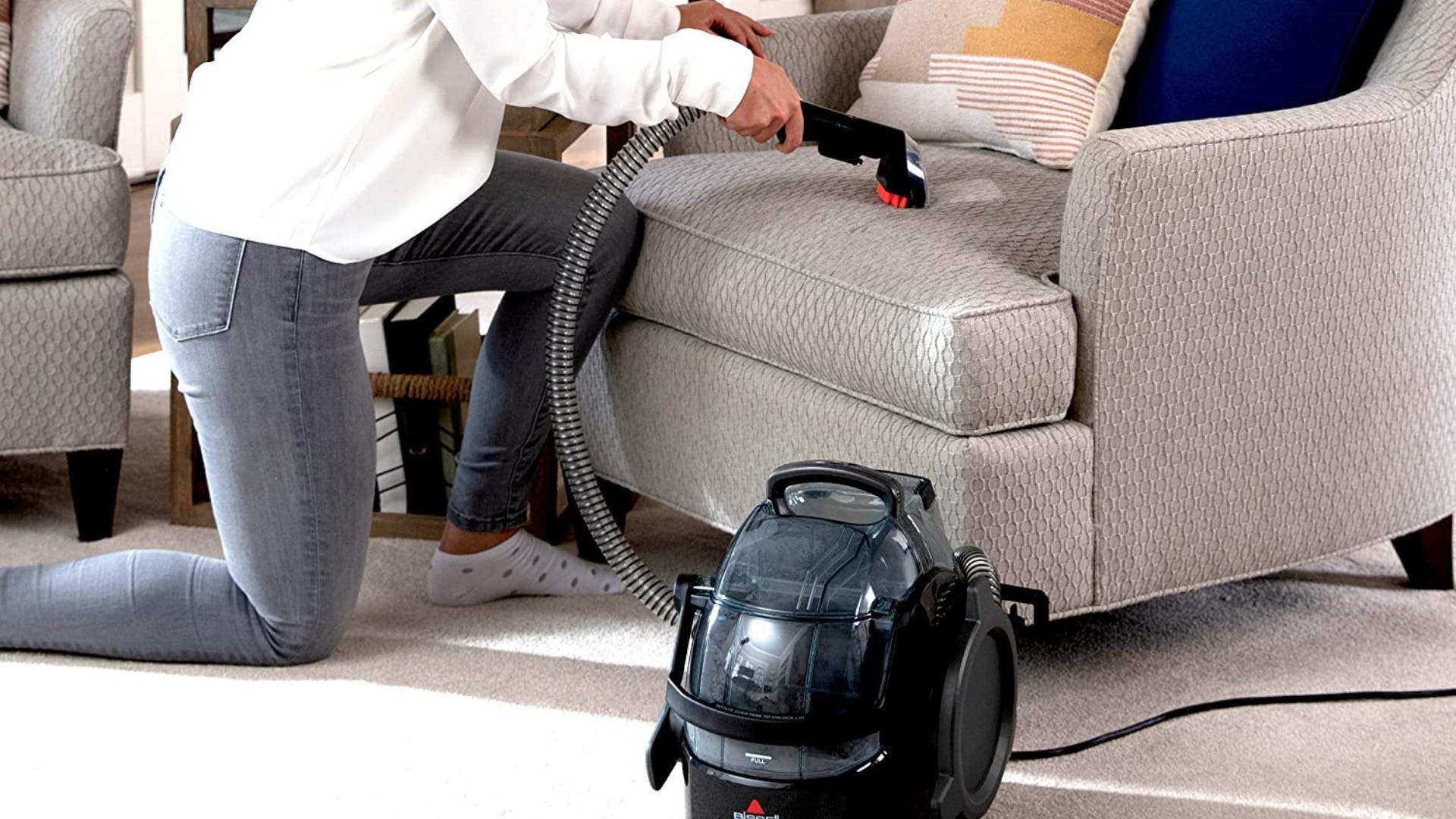 A woman vacuuming the upholstery on a chair with the hose on the Bissell 3624 Spot Clean Portable Vacuum.