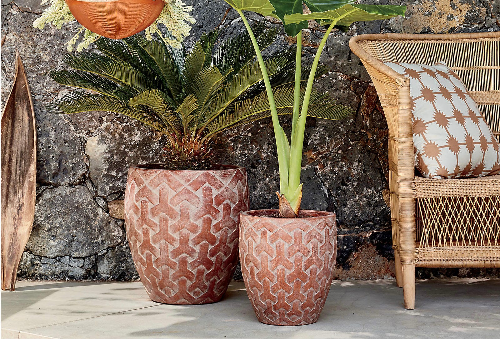 A pair of patterned terracotta planters next to an outdoor chair.