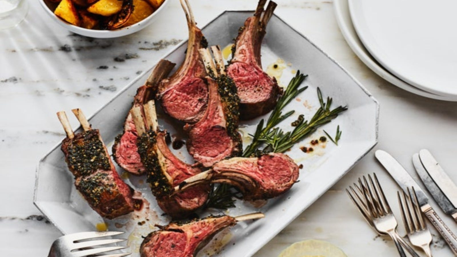 A lovely rectangular plate lined with silver accents serving a rack of medium rare lamb chops freshly cut from a rack of lamb garnished with rosemary.