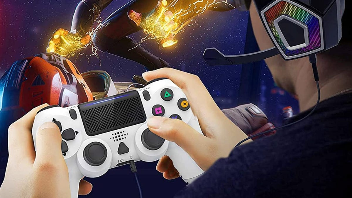 A boy plays a video game with a PS4 controller in his hands and the game on the screen in the background.