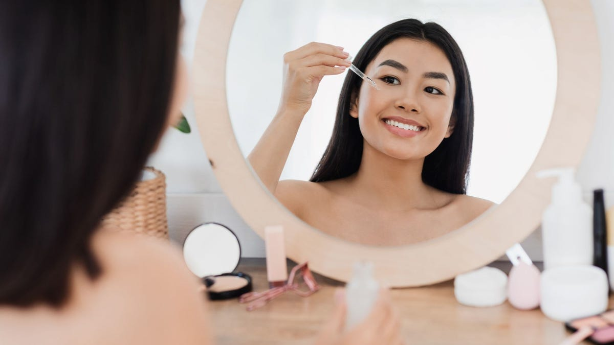 A woman sitting at a vanity and using a dropper to put some Niacinamide serum under her eye.