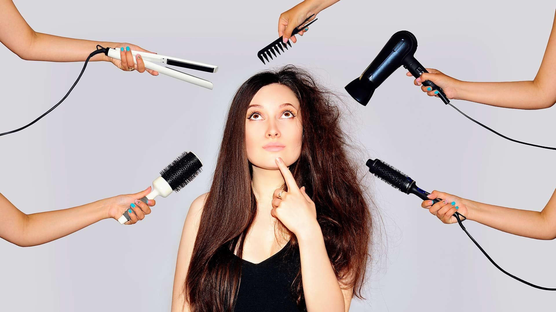 A woman surrounded by hands holding hair styling tools like flat irons, blow dryers, and other heat-damage causing devices.
