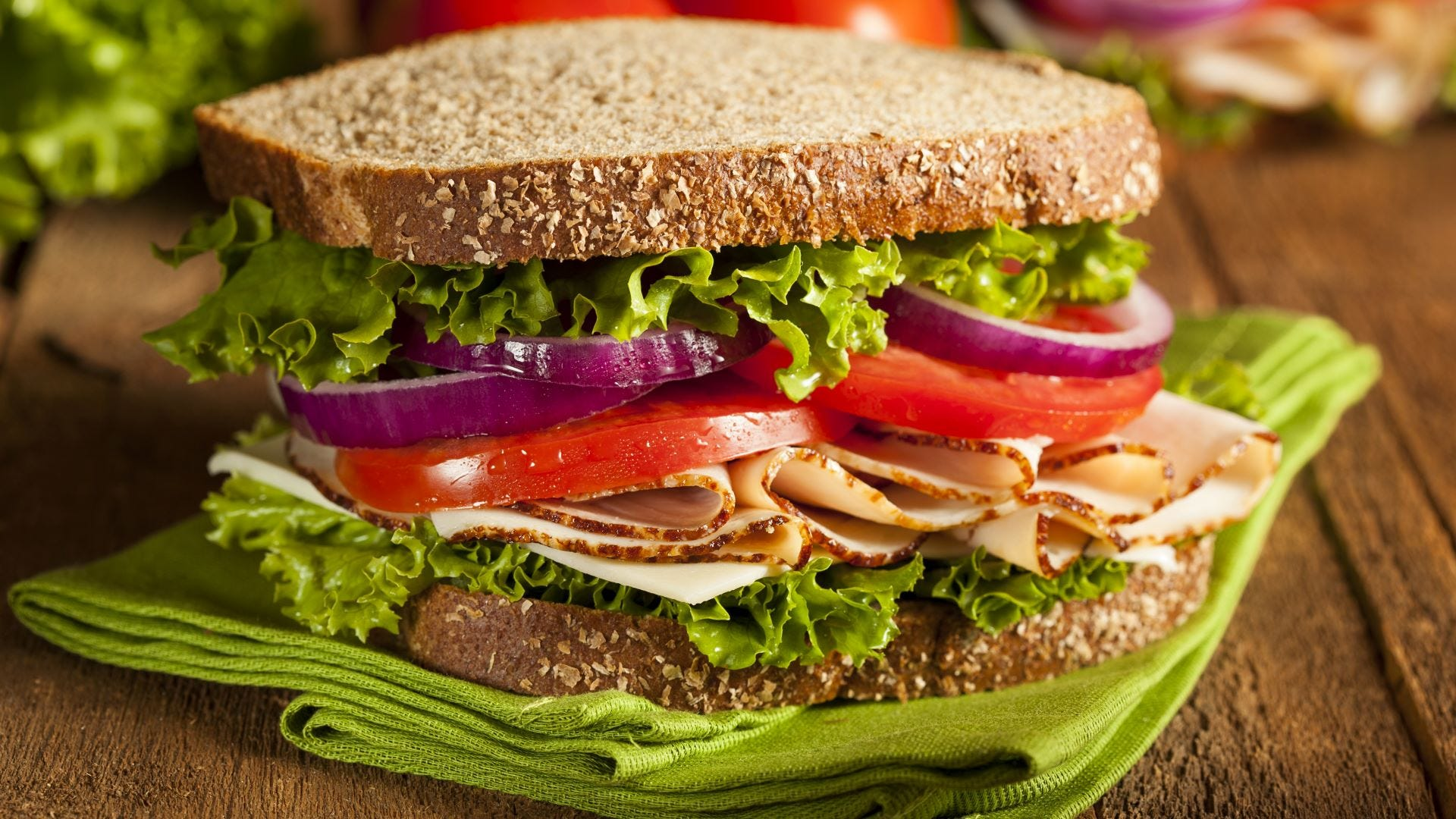 A turkey sandwich on wheat bread with tomato, lettuce, and onion.