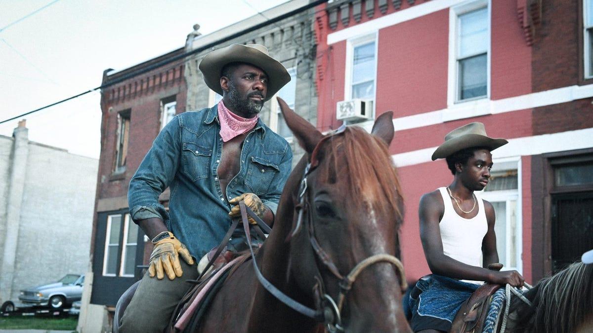 "Idris Elba and Caleb McLaughlin on horseback in a scene from ""Concrete Cowboy."""