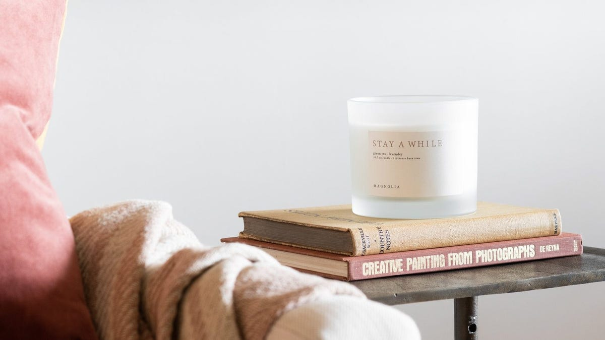 A Magnolia Stay a While candle sitting on top of a stack of books on a side table.