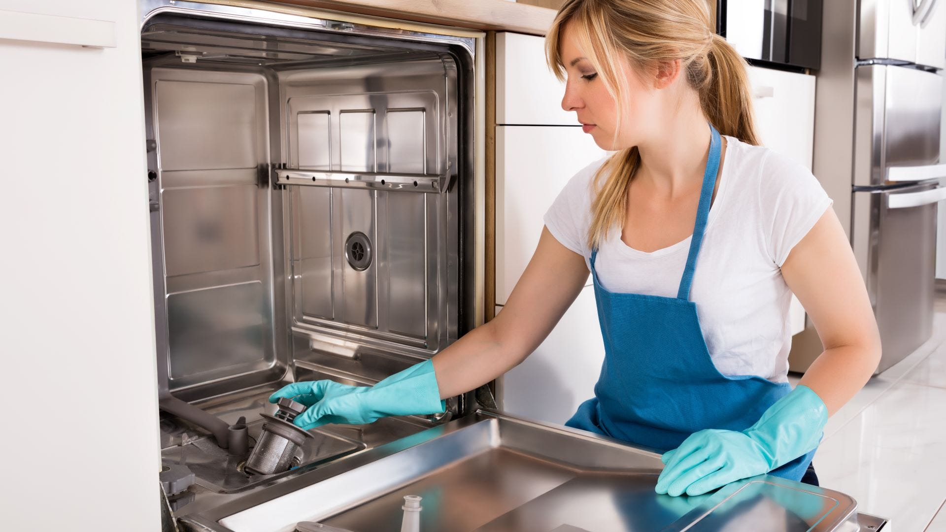 A woman wearing rubber gloves and cleaning a dishwasher.