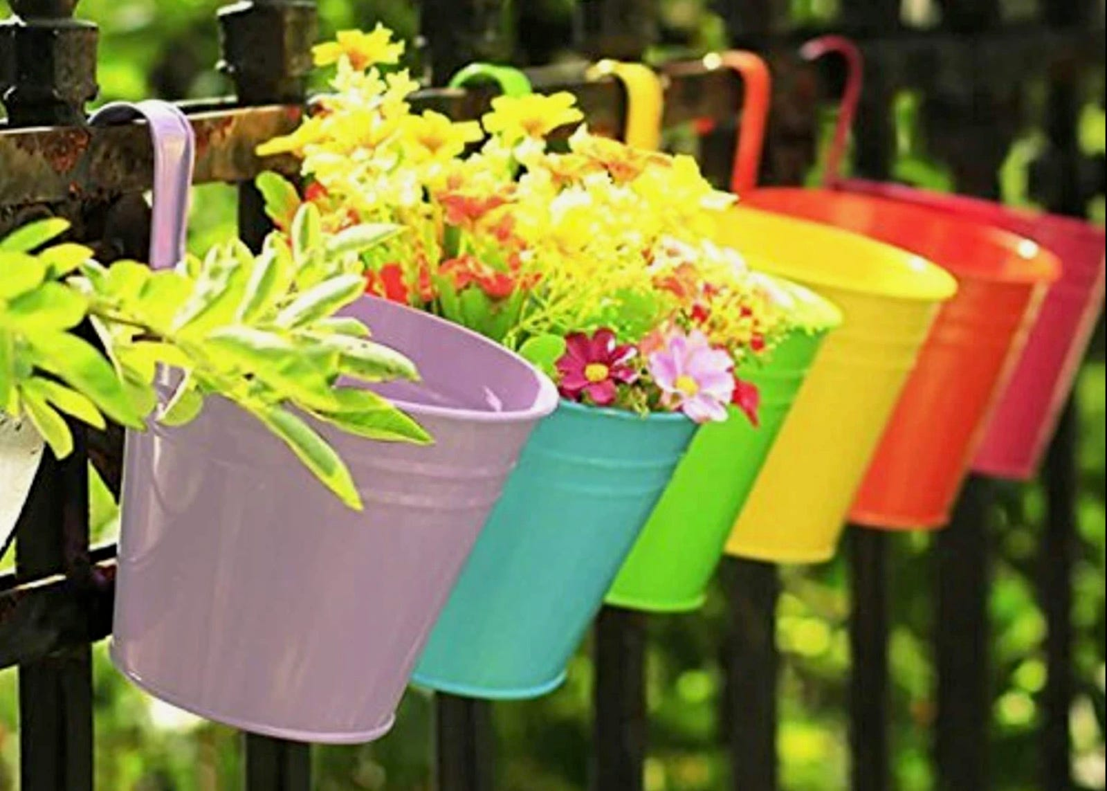 A row of flowerpots in a rainbow of colors hanging from a railing.