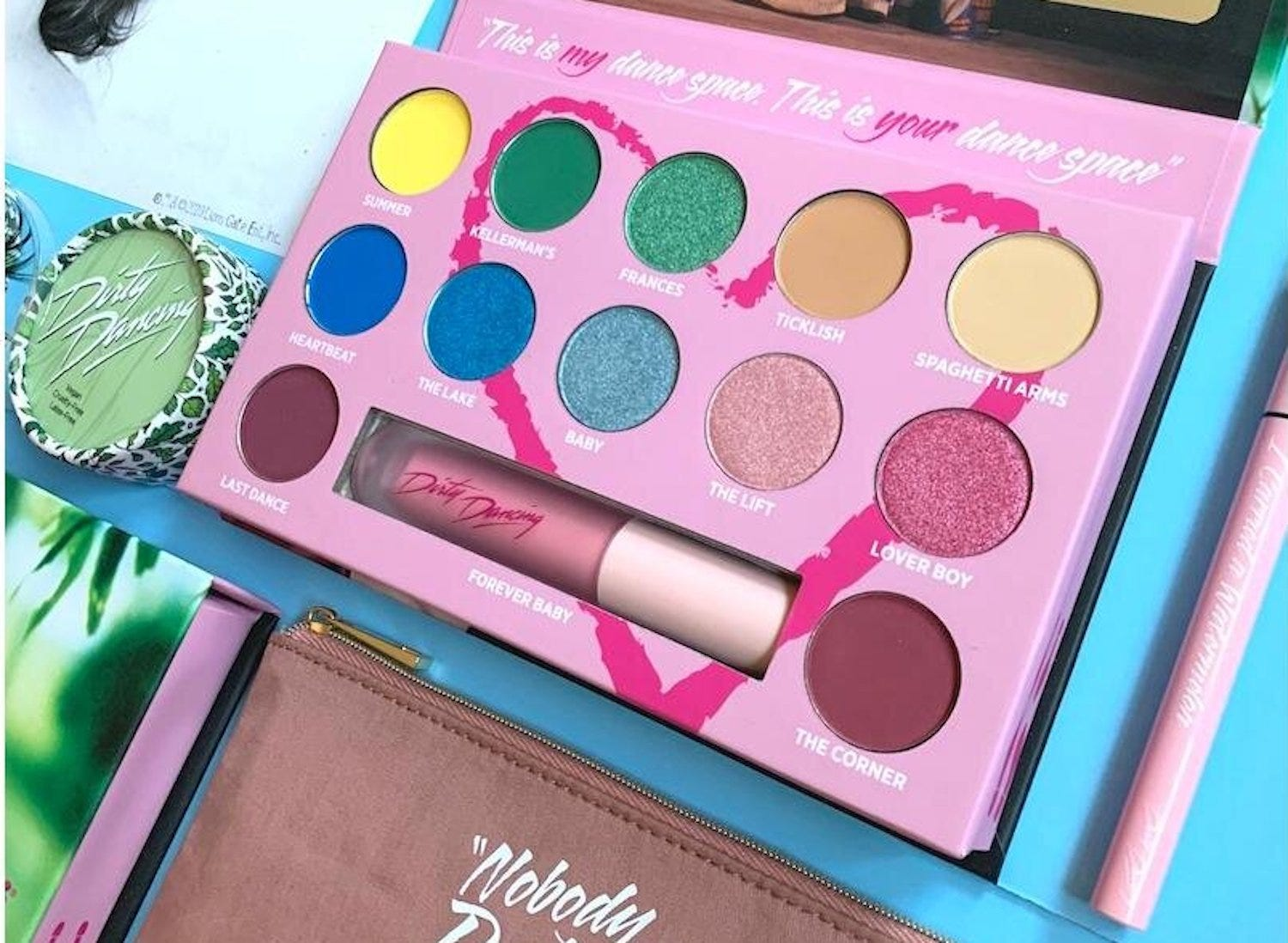 A pink eyeshadow palette with a rainbow of round eyeshadow pots and a pink lip gloss tube