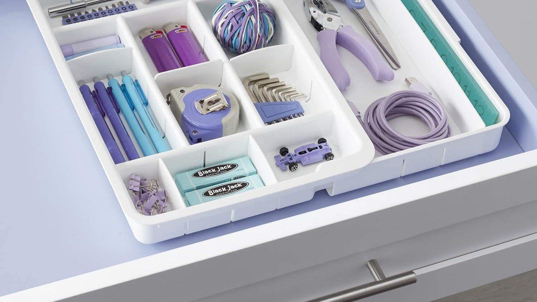 Junk drawer neatly organized using a plastic organizer.