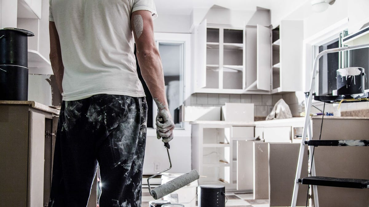 A man covered in white paint after painting his kitchen cabinets.
