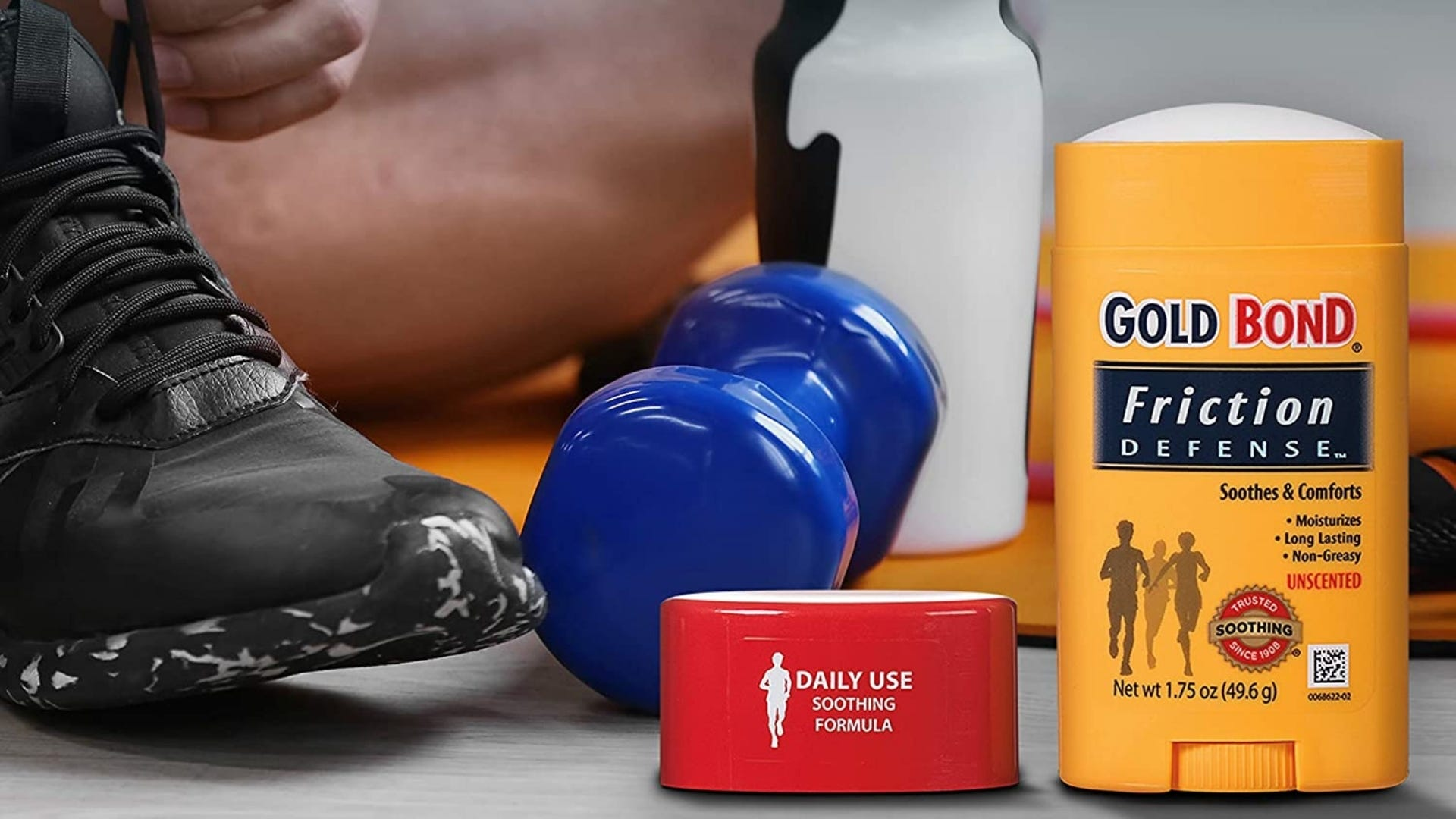 A stick of anti-chafe balm sits on a gym floor.