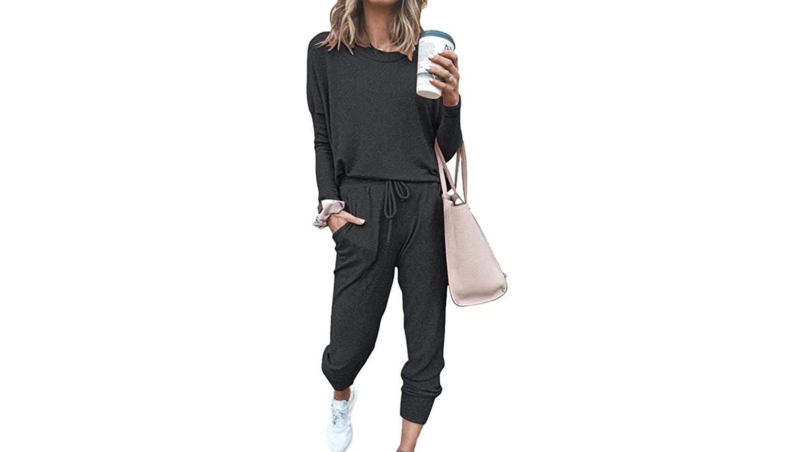 woman wearing black activewear set and holding coffee