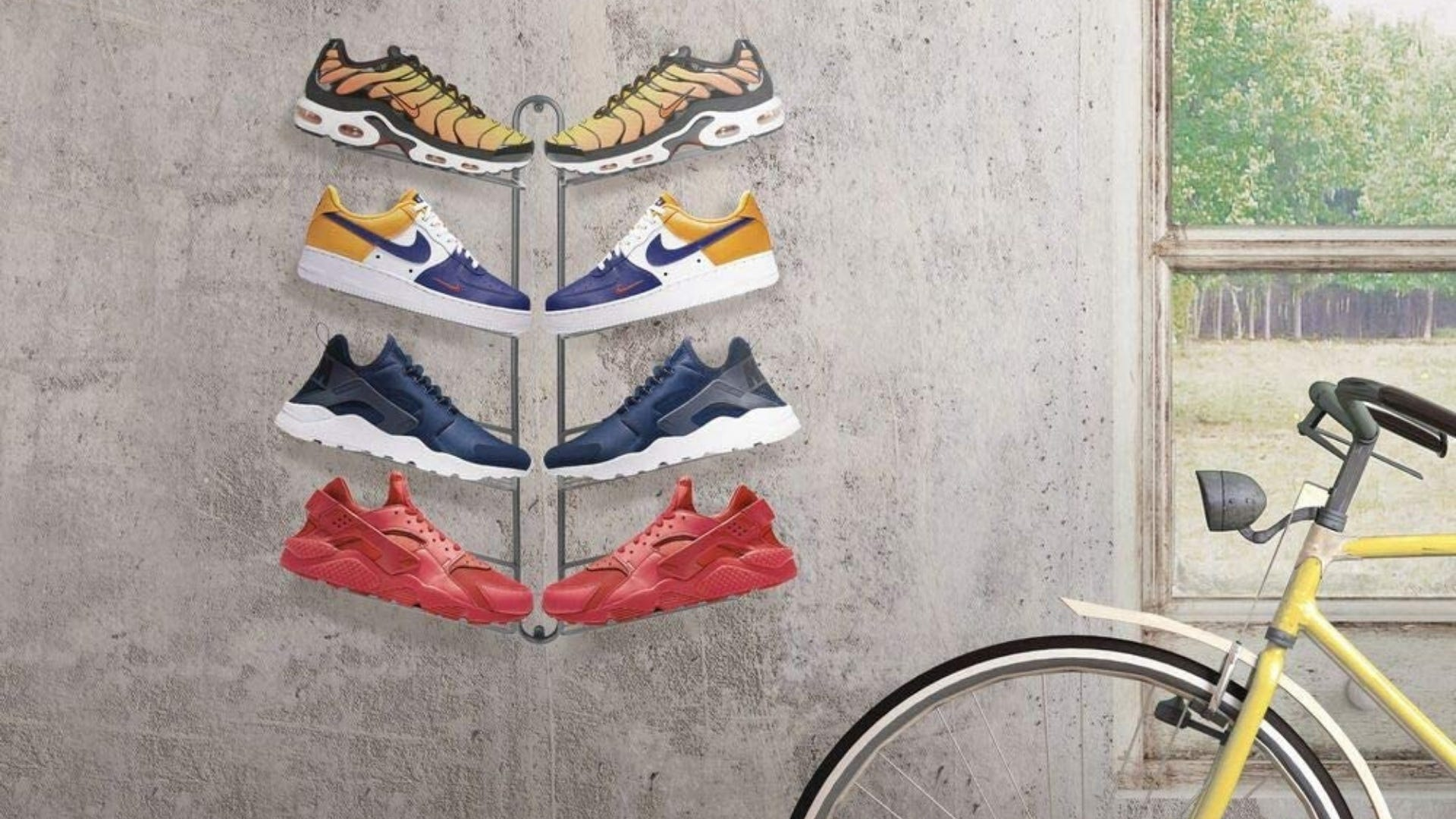 A display rack on a wall holding four pairs of shoes