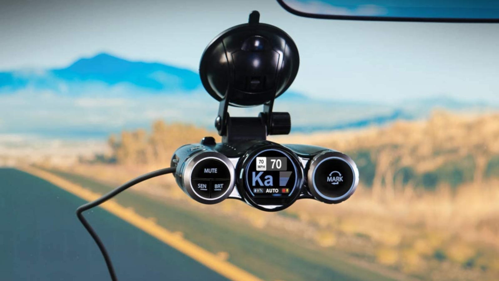 A windshield-mounted black radar detector and a dash cam with a mountain landscape in the background.