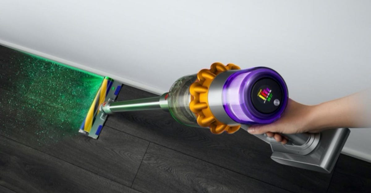 Someone using the green laser on the cordless Dyson V15 vacuum on a hardwood floor.