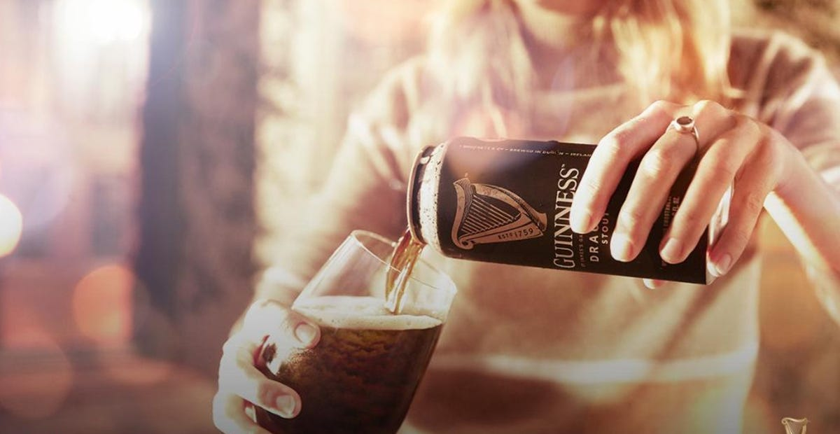A woman pours Guinness from a can into a glass mug.