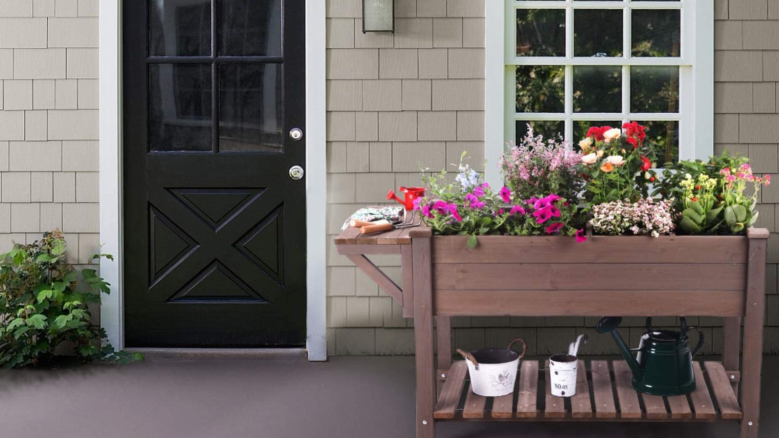 A lovely brown wooden raised garden bed filled with colorful flowers with decorative planters on the bottom shelf and gardening tools place don the side tray, displayed on a patio of a home.