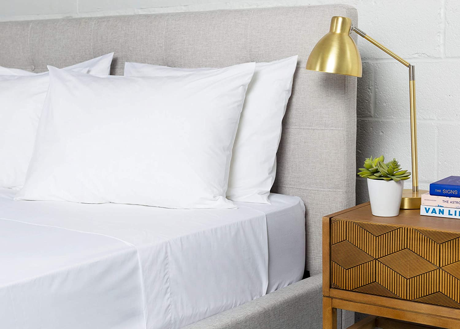 A bed made up with fresh and crisp percale weave cotton sheets.