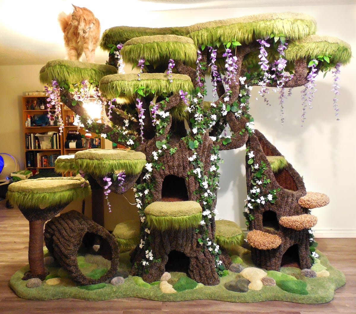 A cat sits on top of a cat tower designed to look like an enchanted tree.