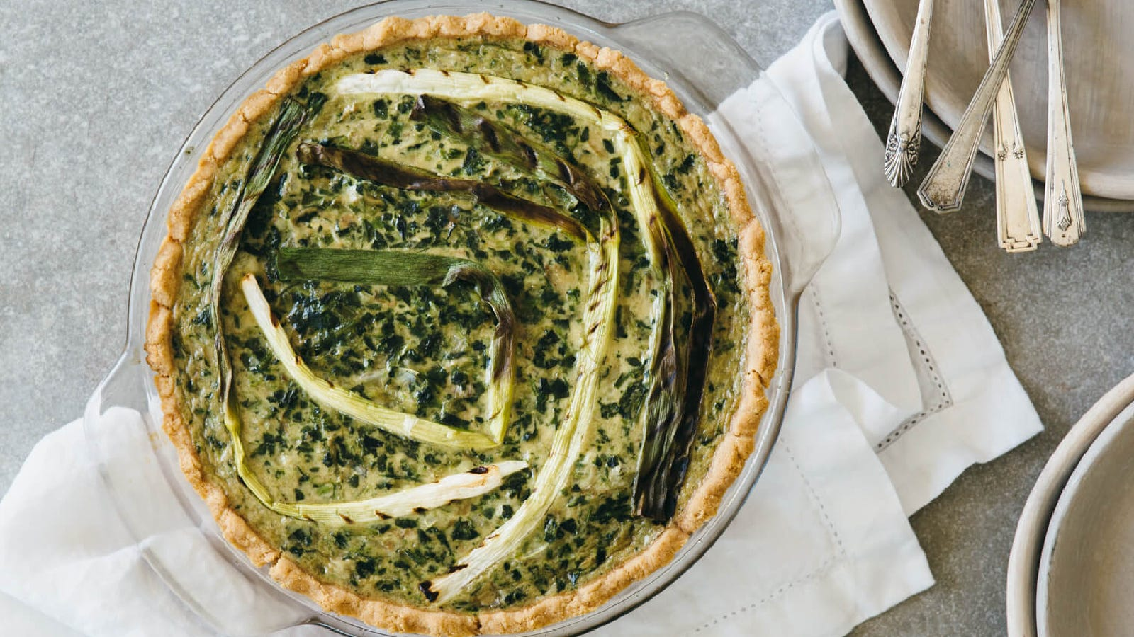 A lovely spring quiche filled with cheese, spinach, artichoke and grilled spring onions.