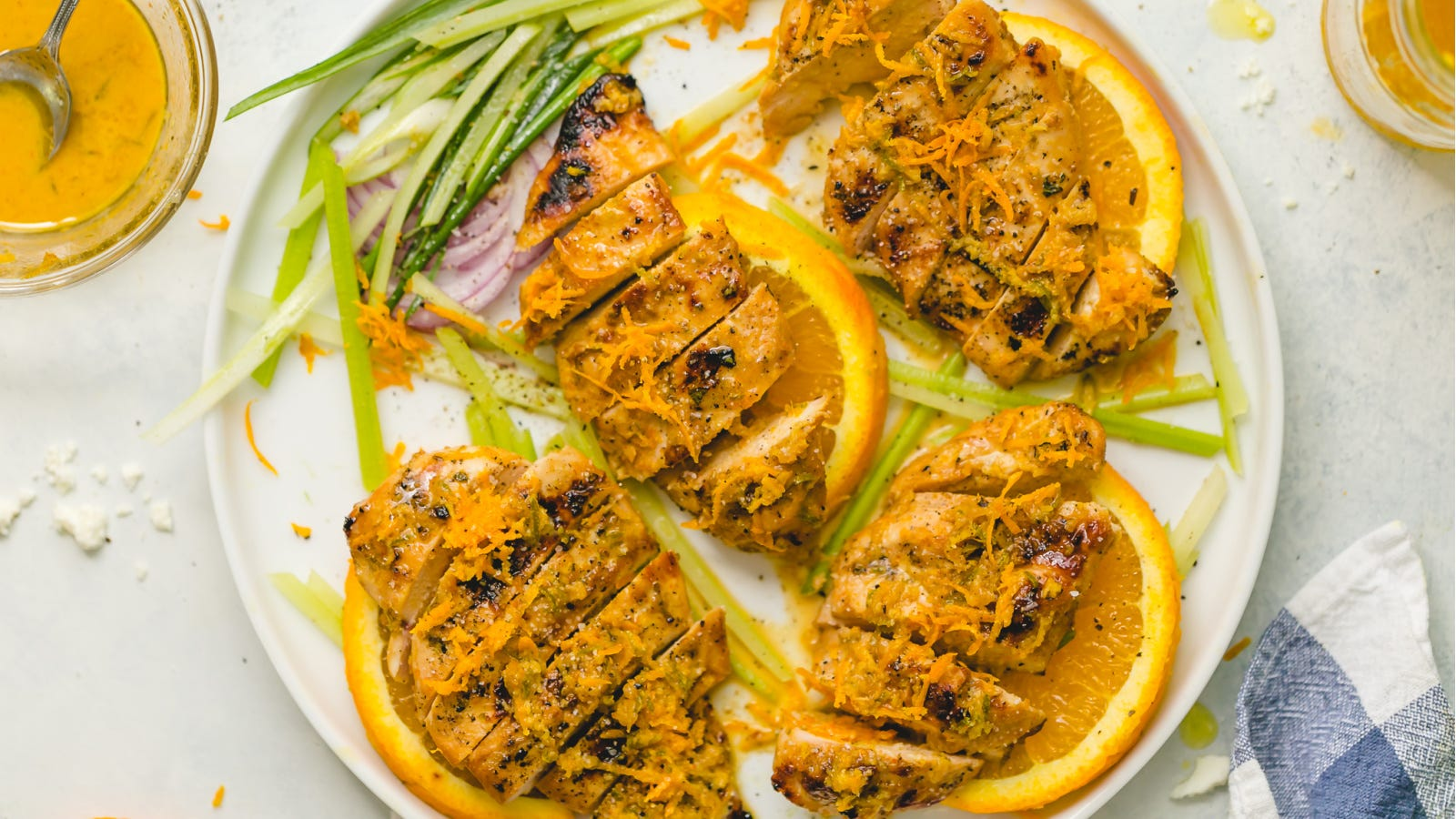 A plate of ginger marinated grilled chicken, topped with orange zest plated with sliced oranges.