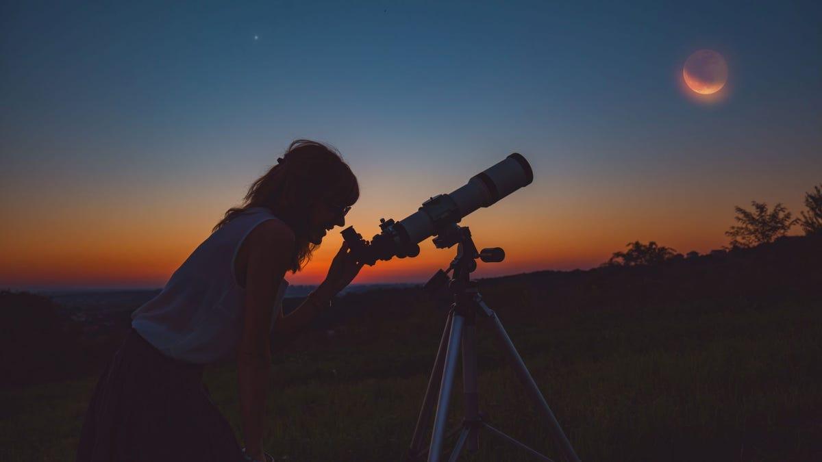 A woman looking at a lunar eclipse through a telescope.
