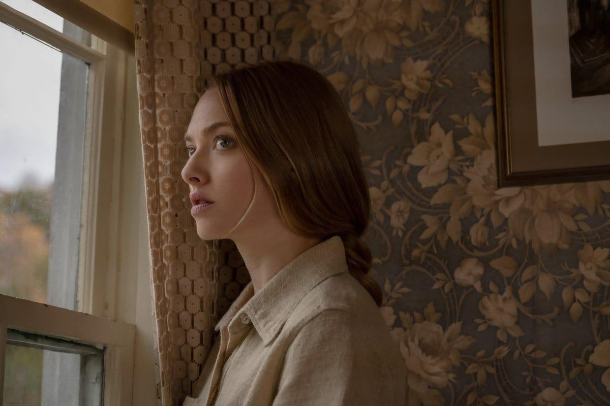"""Amanda Seyfried looking out a window in a scene from """"Things Heard & Seen."""""""