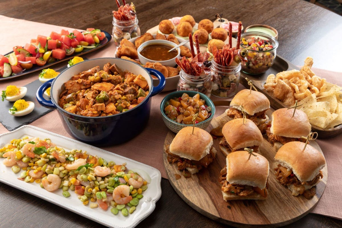 An array of food, including sliders, succotash, and watermelon salad, sit arranged on a wooden table.