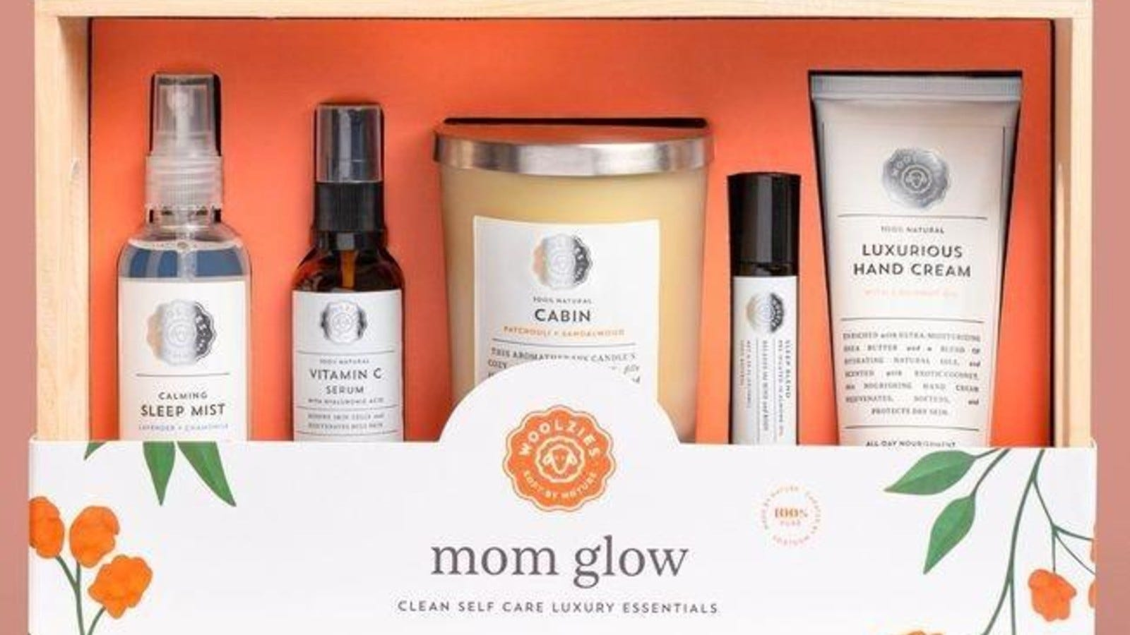 """orange gift box called """"mom glow"""" filled with different skincare products and a candle"""