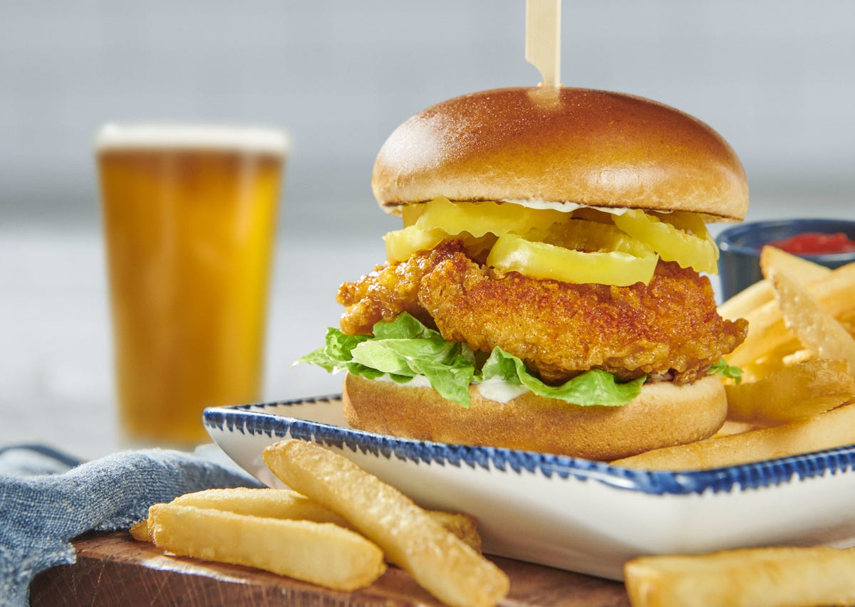 Red Lobster's new chicken sandwich sits on a blue and white plate surrounded by french fries.