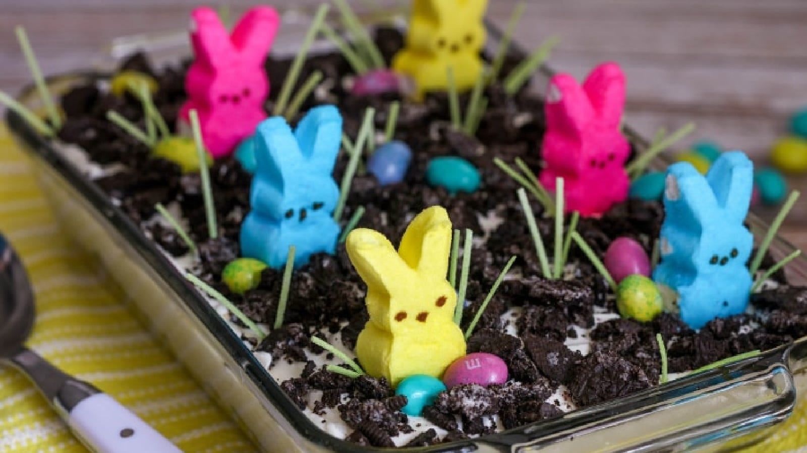 A Pyrex casserole dish filled with Oreo dirt cake, topped with crumbled Oreo's, peeps, edible grass and Easter colored M&M's.