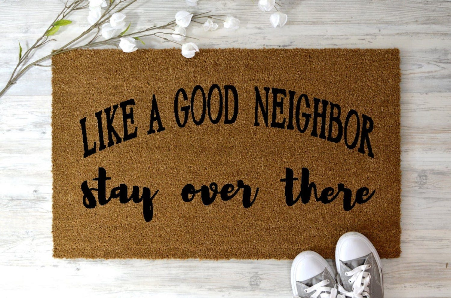 """A doormat reading, """"Like a good neighbor, stay over there"""""""