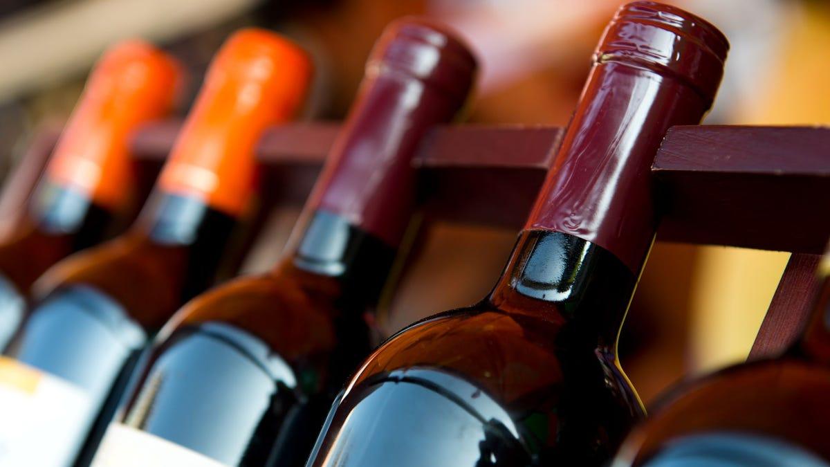 Four wine bottles on a rack.
