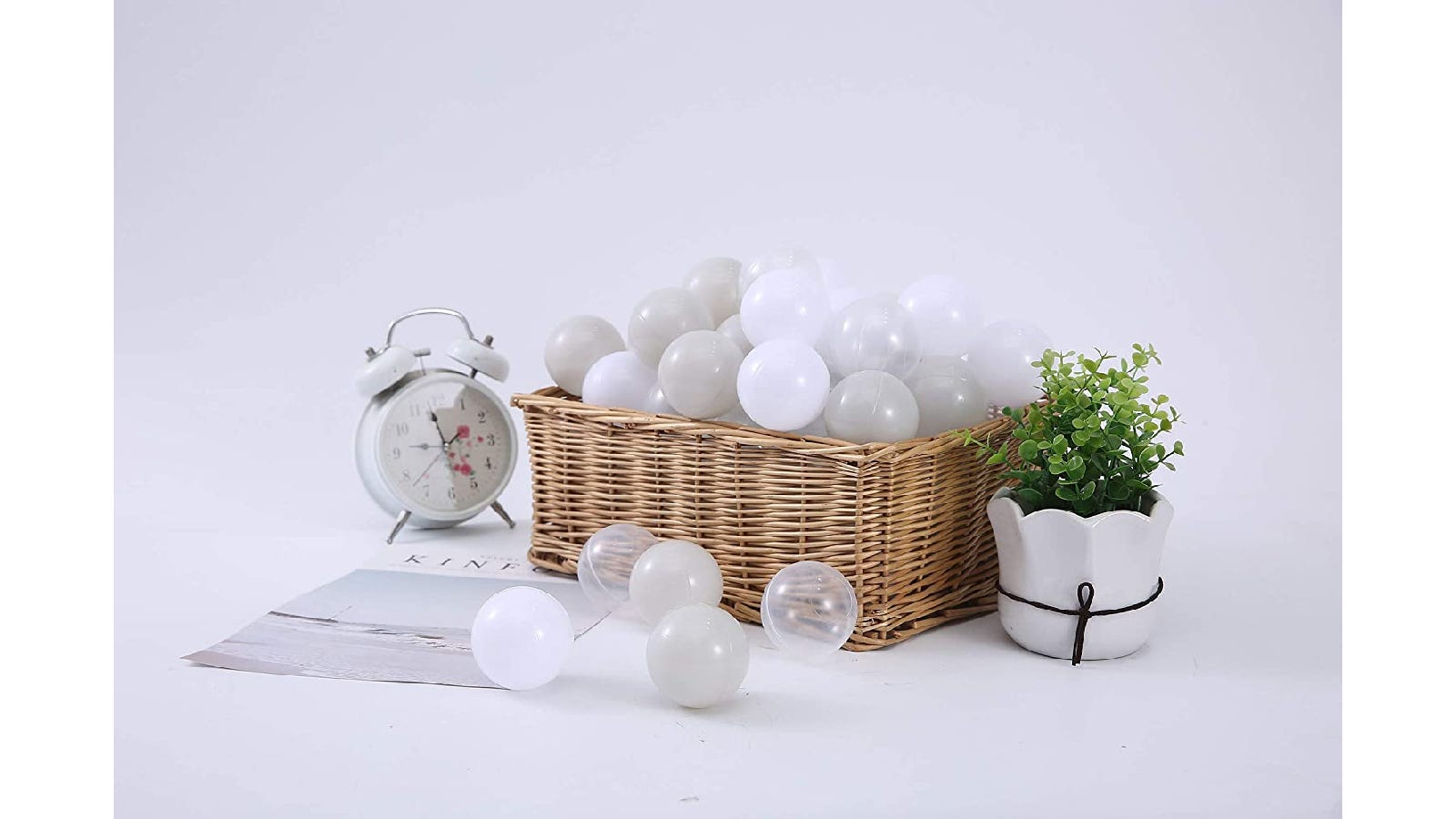woven basket filled with white, gray, and clear plastic balls with a potted plant to the right and a white alarm clock to the left