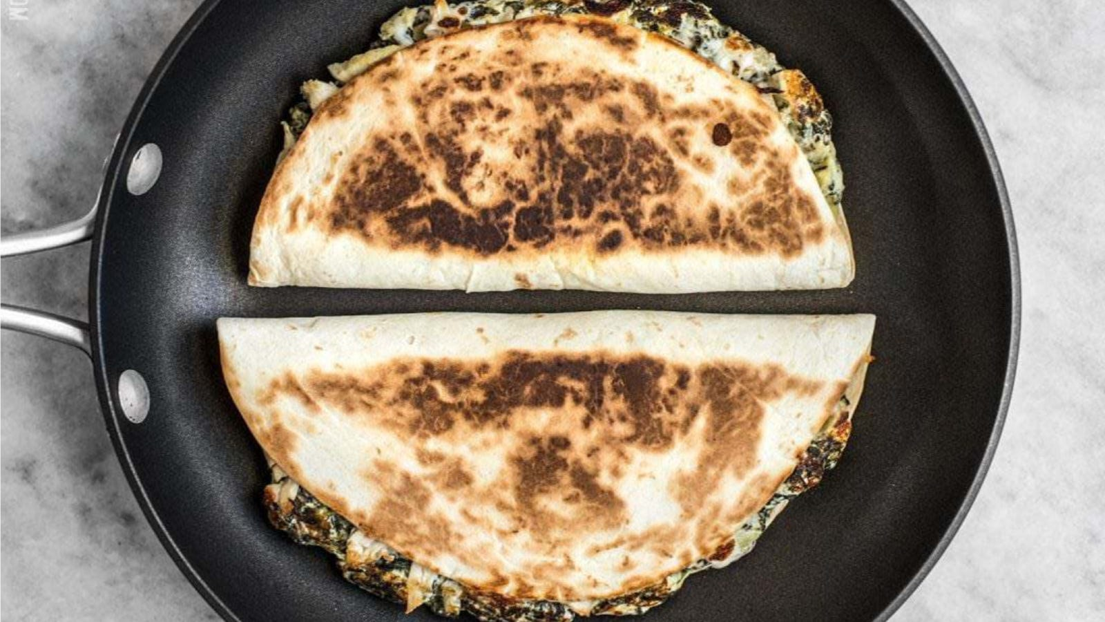 Two quesadilla's stuffed with spinach and artichoke, sitting in a hot skillet ready to be transferred to a cutting board.