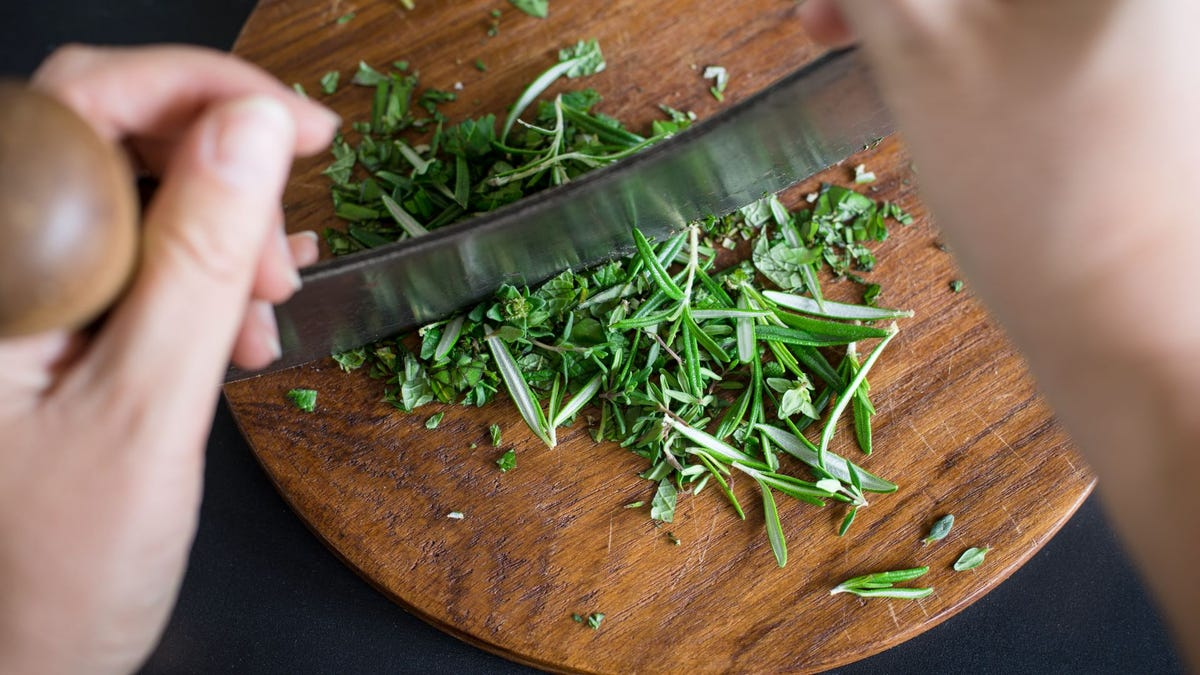 Someone chopping herbs on a wooden chopping block.