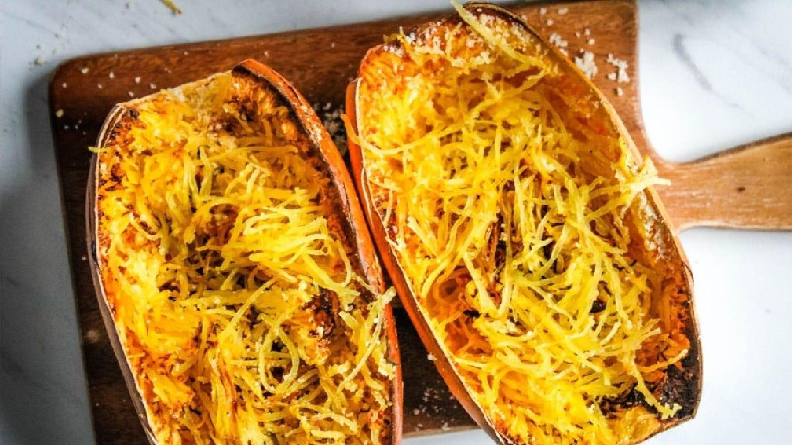 An air fried spaghetti squash sliced in half sitting on a cutting board.