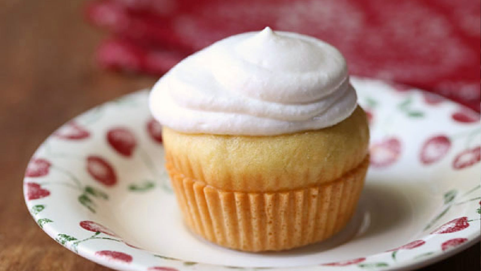 A cupcake topped with yogurt frosting sitting on a plate.