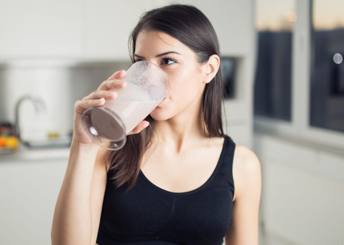 Woman in sportswear drinking a healthy shake