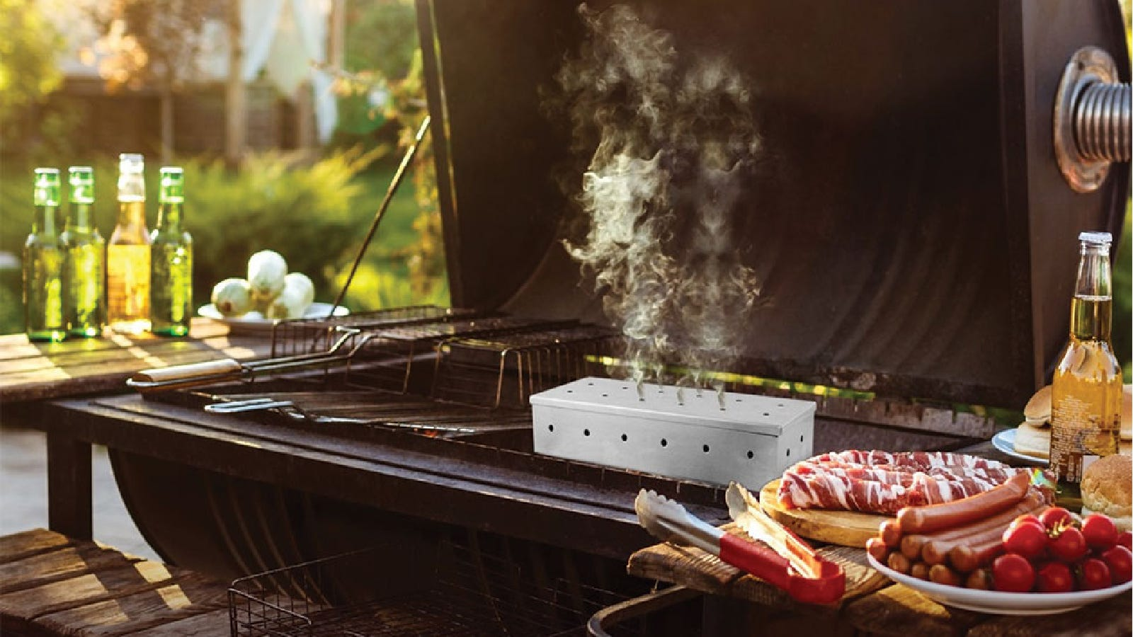 A Kaluns smoker box full in action on a grill smoking with sausage and other ingredients nearby.