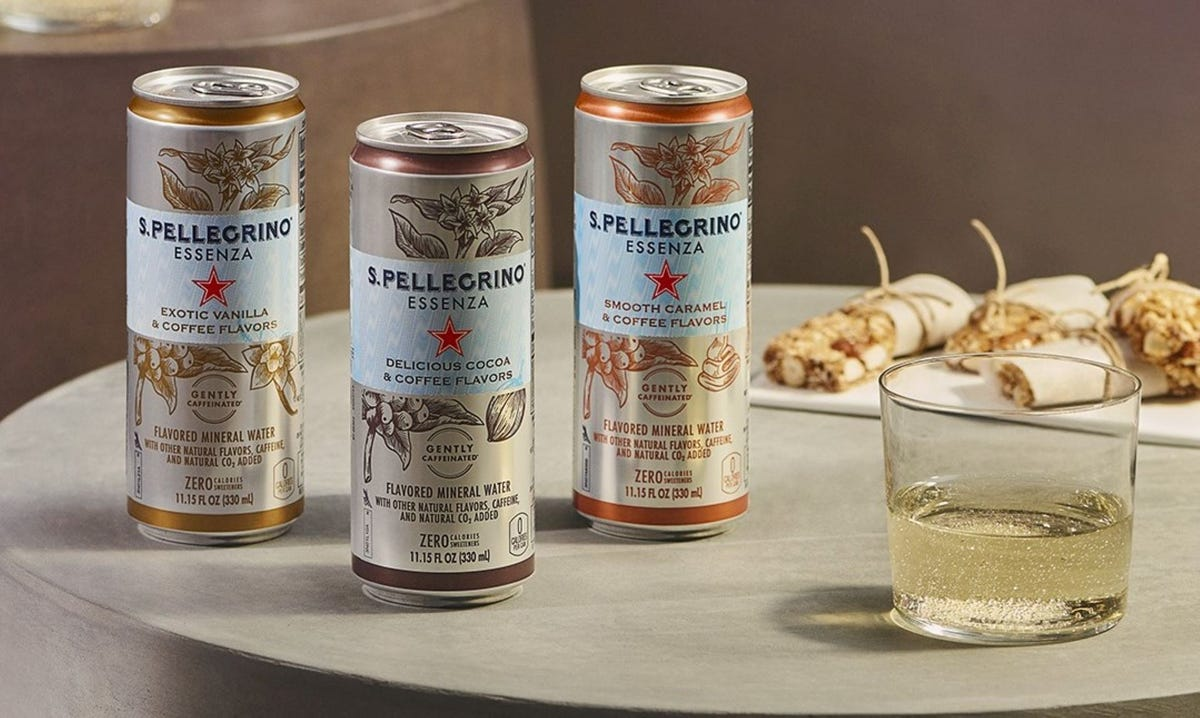 Three cans and a glass of the S.Pellegrino coffee-favored sparkling waters.