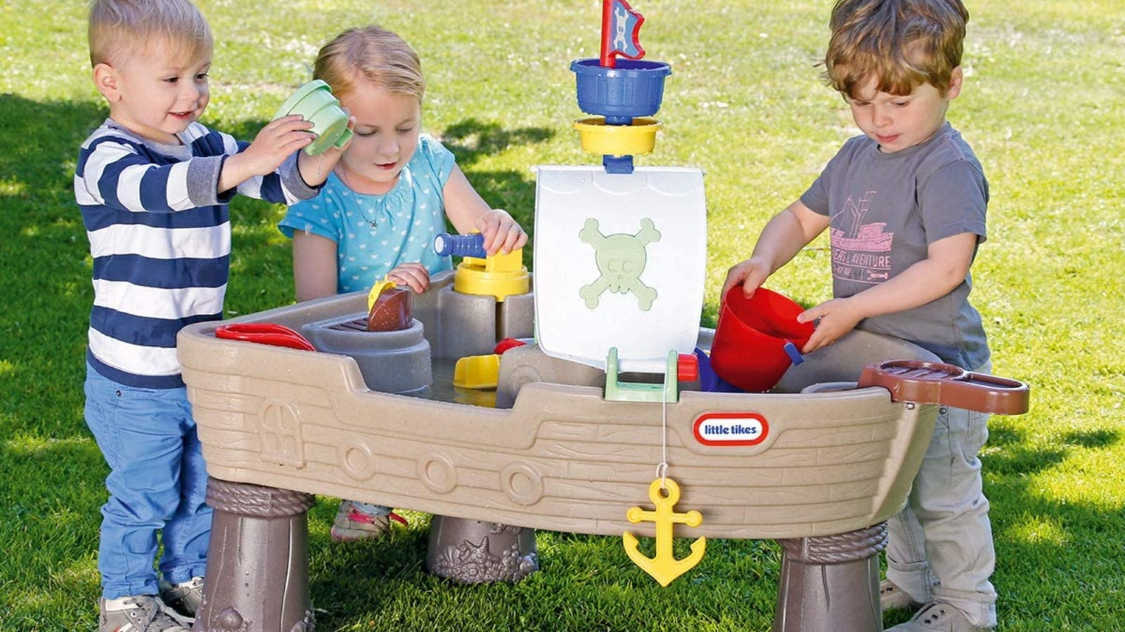 Three young children playing with a Little Tikes water table.