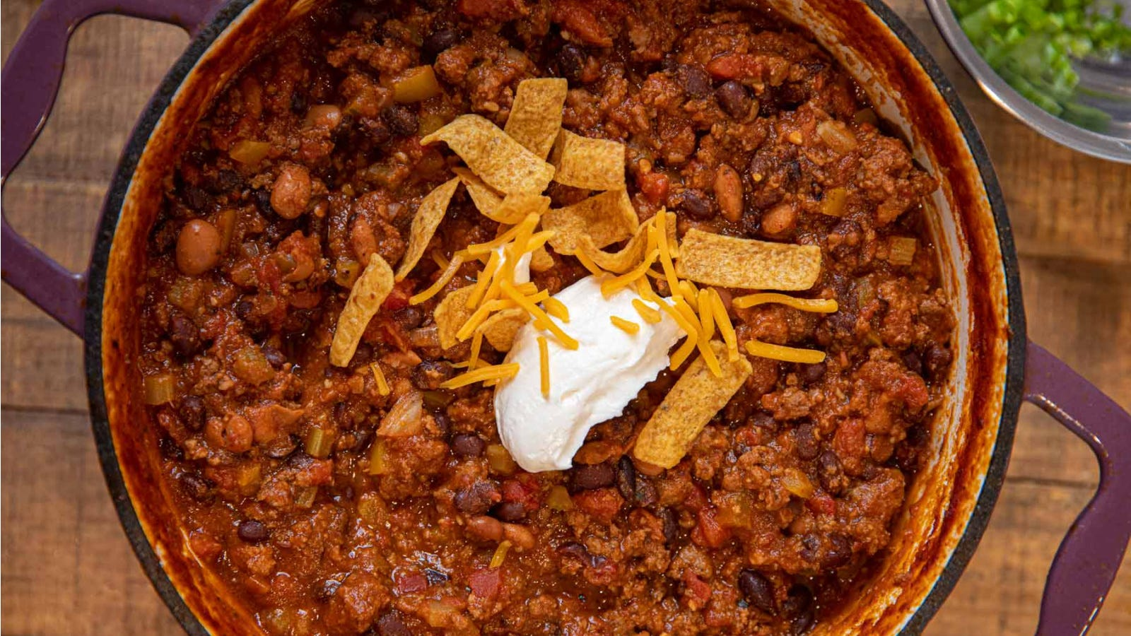 A large dutch oven filled with taco chili, topped with Fritos, cheddar cheese and a dollop of sour cream, with a side of chives.