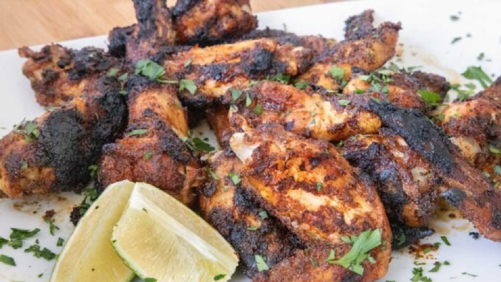 Dry rub chicken wings topped with parsley and garnished with lime wedges.
