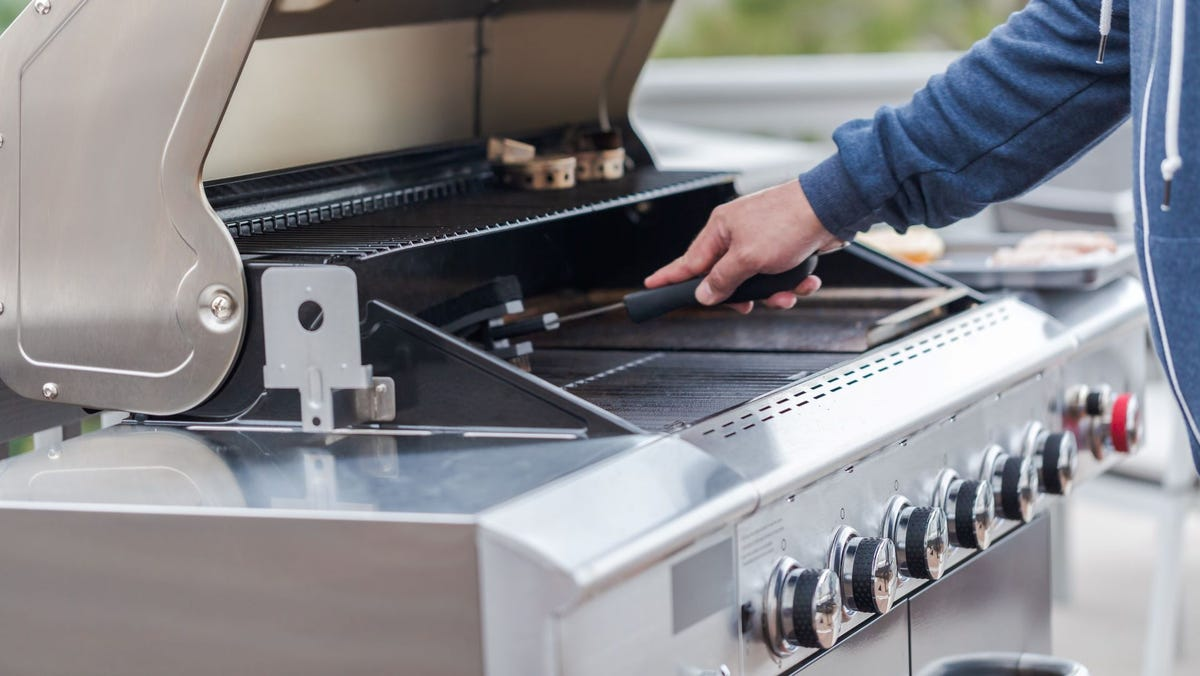 A man cleaning a gas grill.