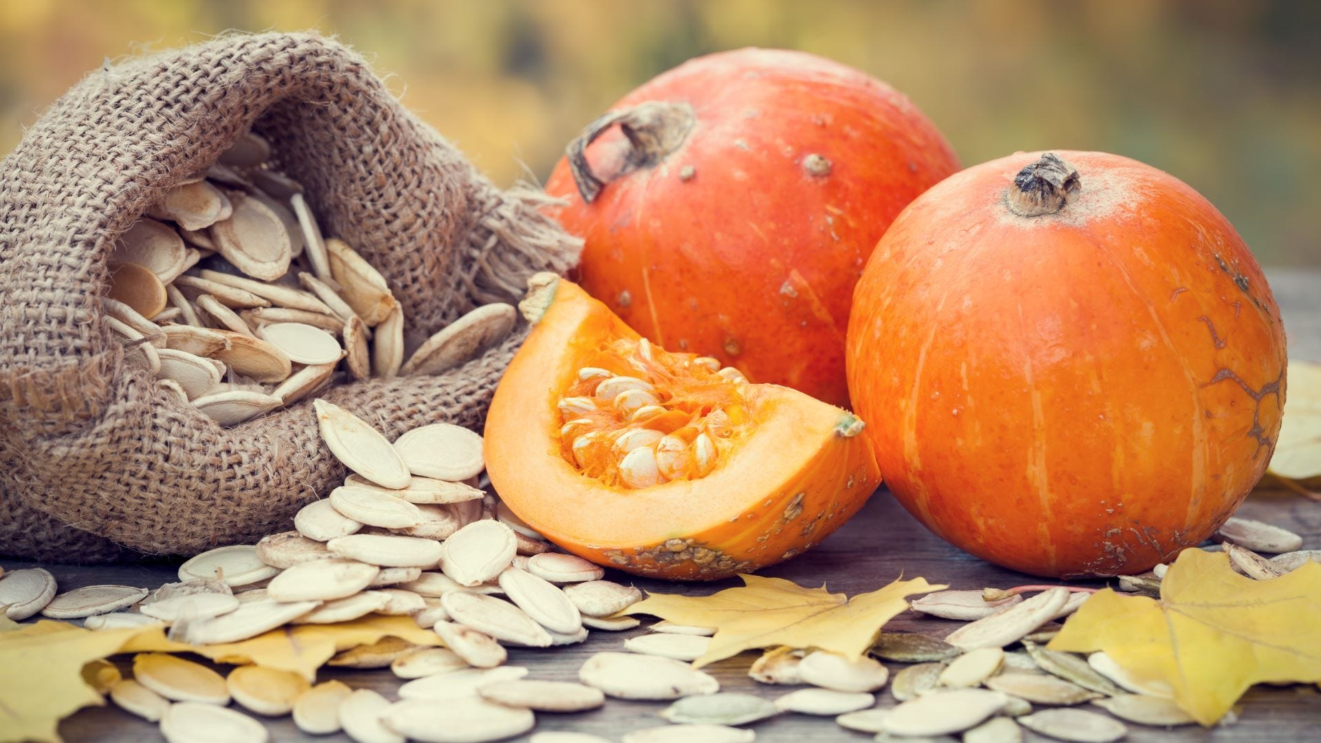 Two small pumpkins surrounded by pumpkin seeds.
